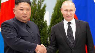 Kim Jong-un und Wladimir Putin schütteln sich vor ihren Landesflaggen Hände