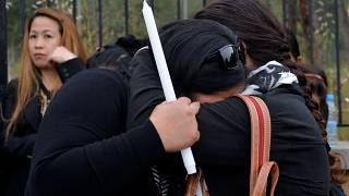 Women hug during a vigil in memory of victims of a suspected serial killer