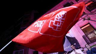 Eine Flagge der PSOE weht vor Pedro Sánchez