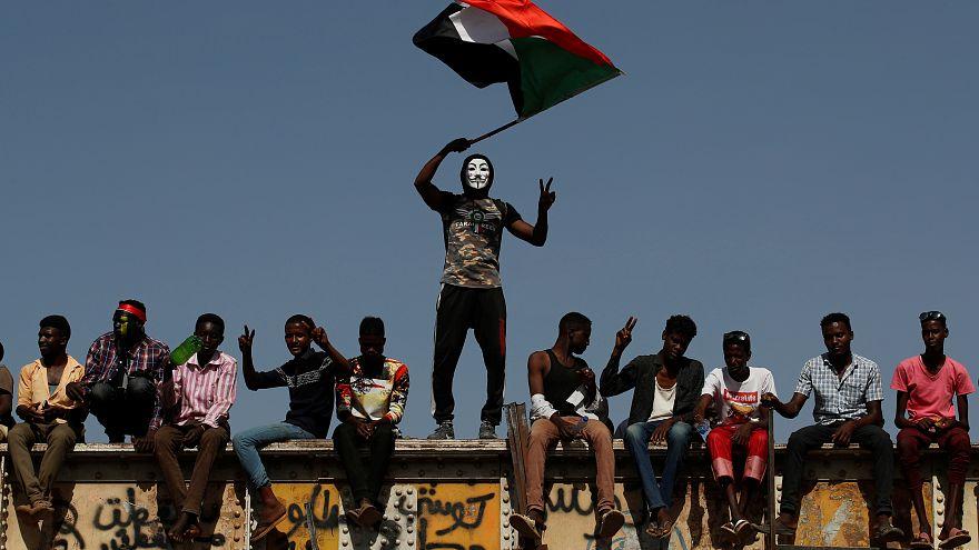 متظاهر سوداني يرتدي قناعا ويلوح بالعلم الوطني