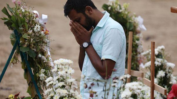 رجل يبدو متأثرا خلال مراسم جنائزية لضحايا هجمات في كنيسة في نجومبو