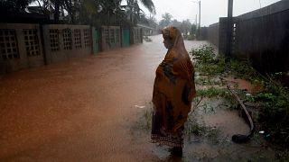 Eine Frau steht in Pemba vor einer überschwemmten Straße