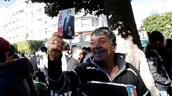 رجل يحمل صورة الرئيس السابق زين العابدين بن علي خلال الاحتفال بذكرى الثورة