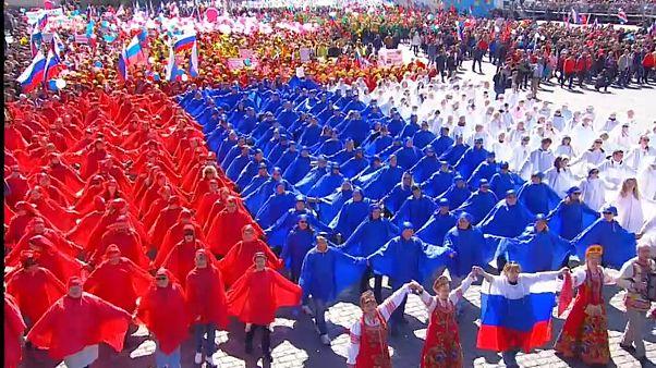 Paradeteilnehmer sind in den russischen Nationalfarben gekleidet
