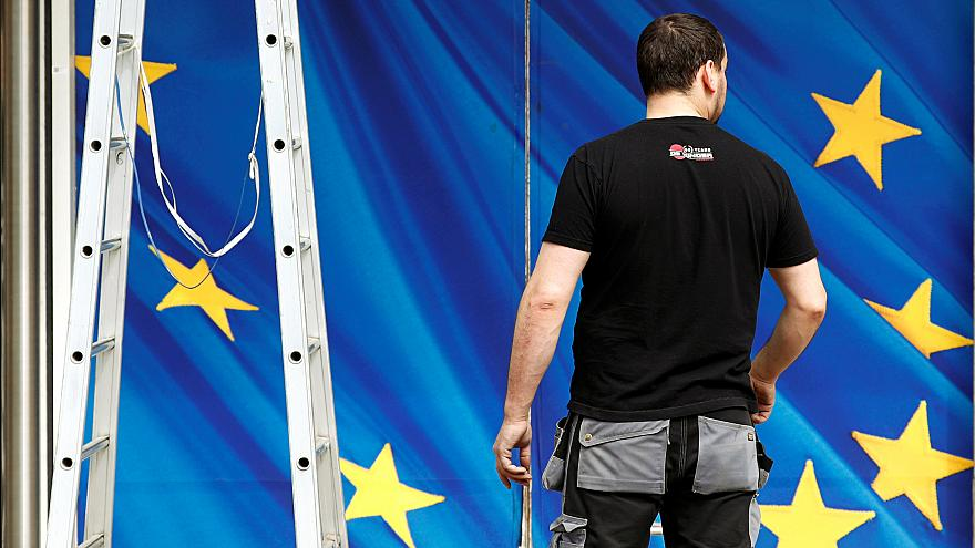 A worker is pictured in front of an entrance to the EU Commission HQ