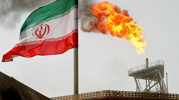 العلم الإيراني وفي الخلف مدخنة منشأة نفطية
