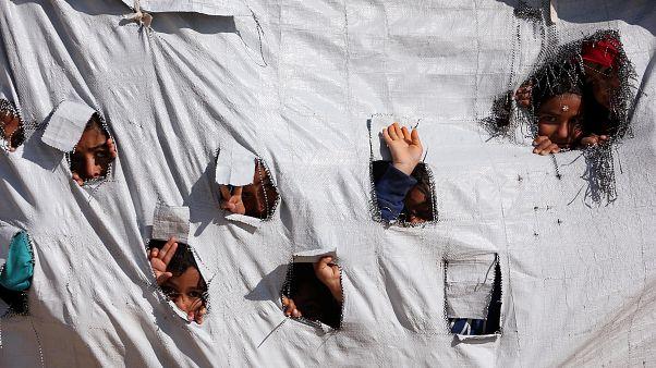 Enfants sortant leurs têtes d'une tente dans le camp d'Al-Hol