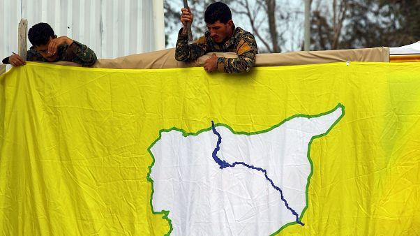 مقاتلان من قوات سوريا الديمقراطية يرفعان علم القوات في دير الزور
