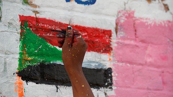 محتج سوداني يرسم على جدار مجاور لمقر وزارة الدفاع في الخرطوم