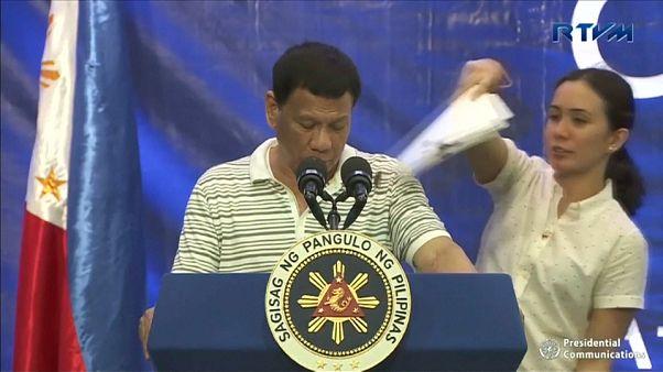 مساعدة للرئيس الفلبيني تحاول إبعاد صرصور حط على كتفه
