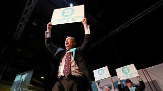 """Nigel Farage hält ein Schild: """"change politics for good"""""""