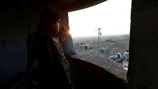 مقاتل من قوات الحشد الشعب يقف عند نقطة مراقبة حدودية في العراق