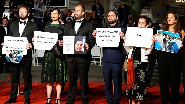 المخرج البرازيلي جوليانو دورنيليز يحمل صورة للمخرج الكولومبي ليزاما
