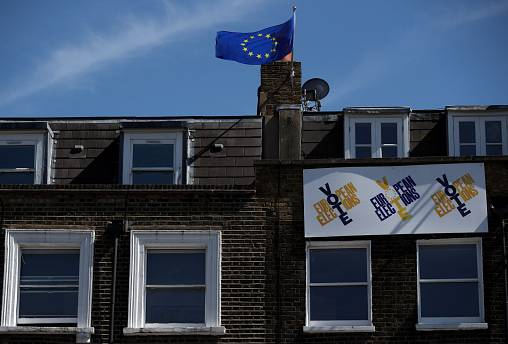 An EU flag flies and a Vote EU Election sign hangs from a house in London.