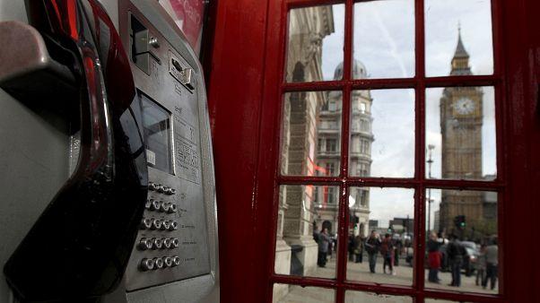 مشهد لمبنى الحكومة البريطانية يلوح من داخل كشك للهاتف الأحمر في لندن