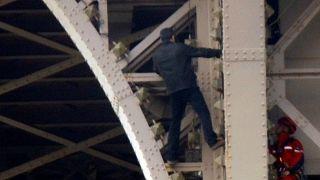رجل يتسلق برج ايفل في باريس ويظهر في الصورة على مستوى زاوية المعلم