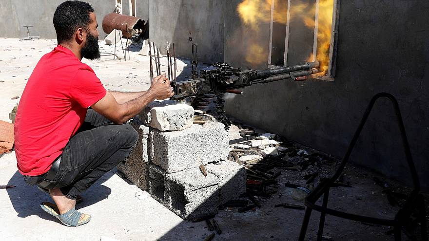 A fighter fires a heavy machine gun during clashes with Haftar's forces