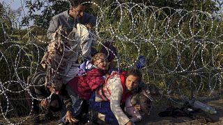 پناهجویان در حال عبور از حصار مرز مجارستان و صربستان