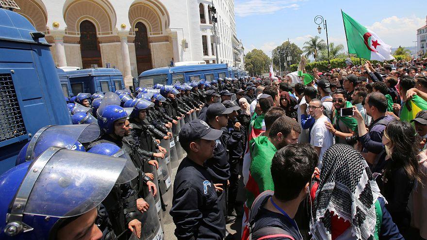 أفراد من الشرطة يقفون حراسة فيما يحتج طلاب ضد الحكومة في الجزائر