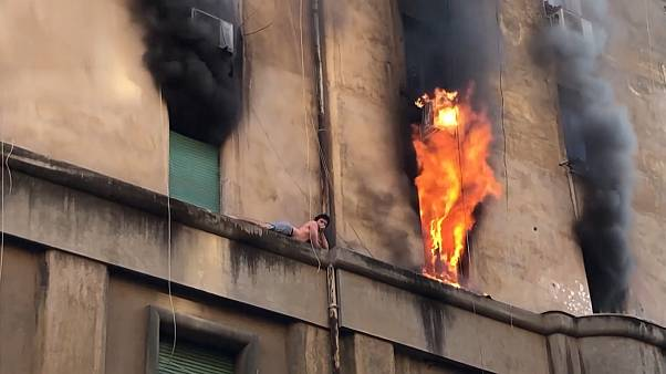 Man clings onto ledge as building burns in Rome
