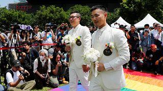 Gay newlyweds walk on a giant rainbow flag in Taipei on May 24, 2019.