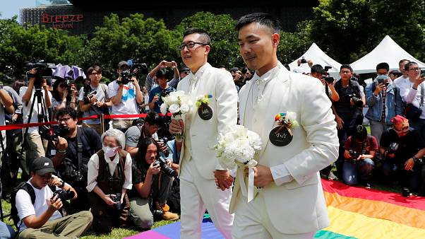 Gay newlyweds walk on a giant rainbow flag in Taipei on May 24, 2019.