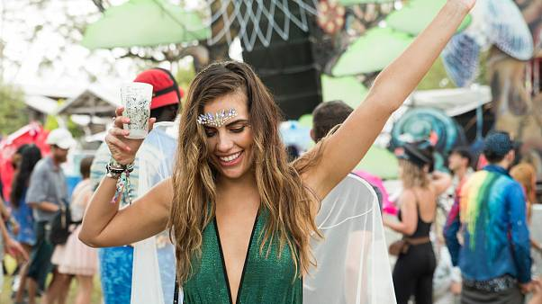 Festival goer dances with drink in hand.