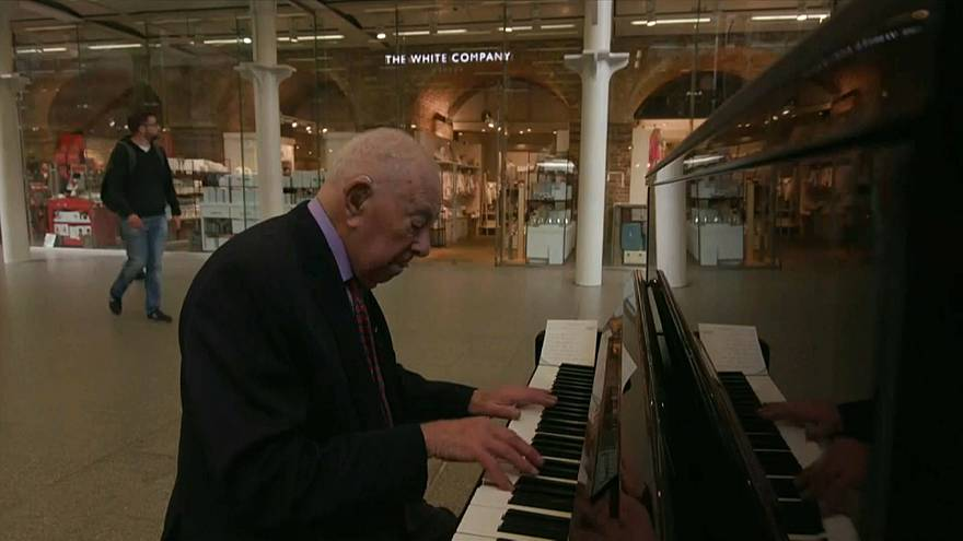 Denis Robinson playing the piano at London St Pancras station