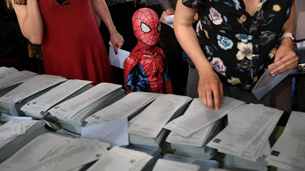 A child in a Spiderman costume stands next to a ballot table for the European Parliament election at a polling station in Madrid, Spain