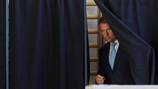Romanian President Klaus Iohannis leaves a polling booth