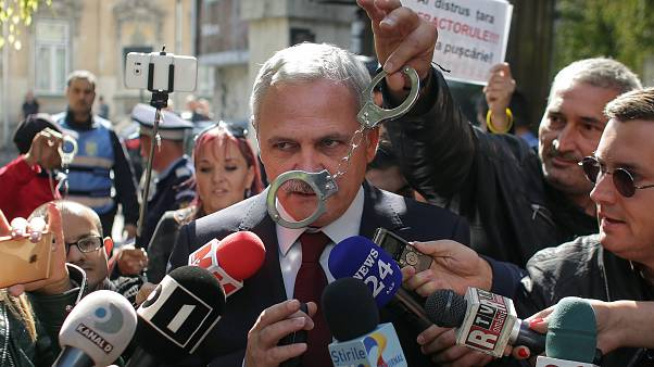 Liviu Dragnea has handcuffs waved in front of him by Romanian protesters