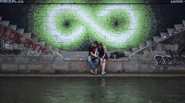 Egy pár ül a Duna partján Bécsben 2017 nyarán