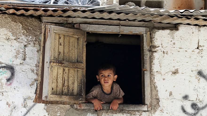 طفل فلسطيني ينظر من نافذة منزله في مخيم خان يونس جنوب غزة