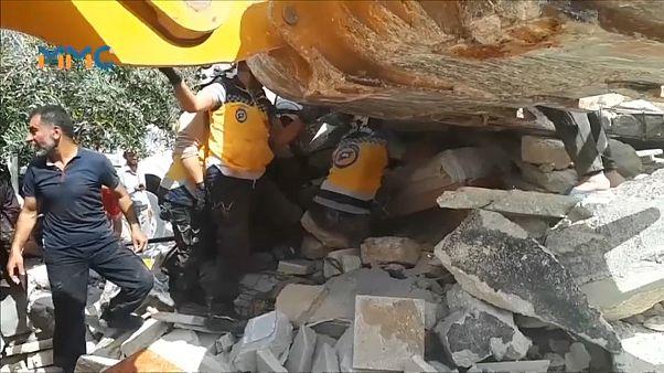عناصر من القبعات البيضاء يتعاونون مع مدنيين لانتشال الفتى من تحت الأنقاض