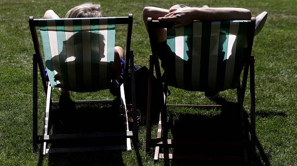 People sit in St James's Park during sunny weather in London, Britain