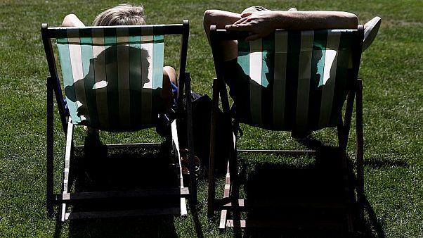 شخصان يستمتعان بأشعة الشمس في برايتون بالعاصمة البريطانية لندن