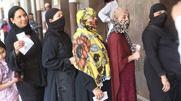 Indiai nők várakoznak egy szavazóhelyiség előtt Újdelhiben
