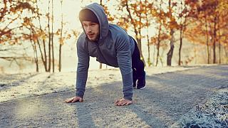 Young runner doing push ups exercise during cold autumn morning