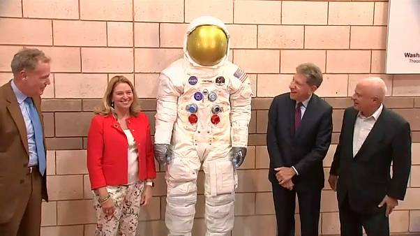 مسؤولون أميركيون بجانب مجسم بدلة رائد الفضاء نيل أرمسترونغ