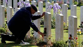 A man places a flower on a tomb at Commonwealth War Cemetery in Bayeux