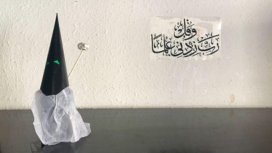 Capirote de Semana Santa hecho con papel.Al fondo, una inscripción coránica