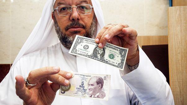 مواطن كويتي يحمل ورقة نقدية لدولار أميركي وأخرى لخمس ليرات تركية/آب-2018
