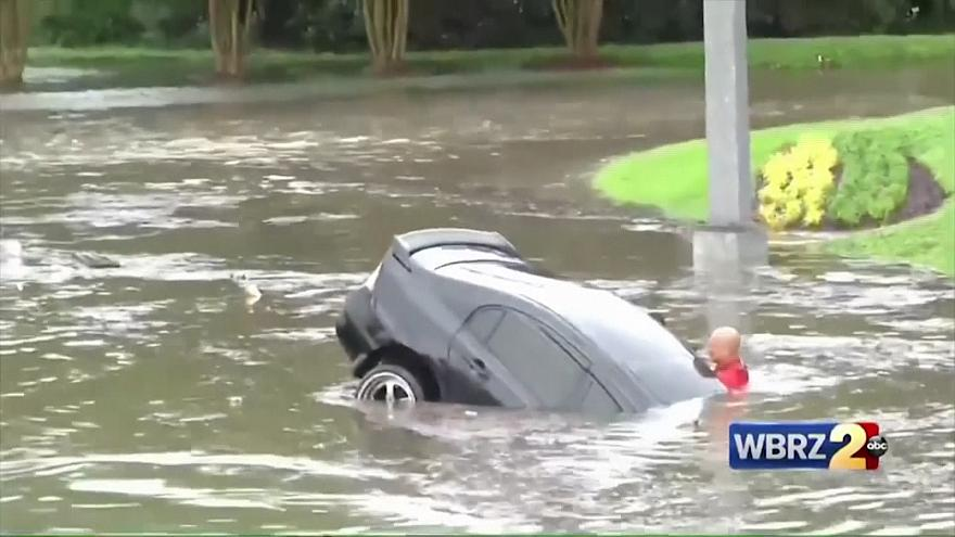 Firefighters save driver after car swept away in flash floods