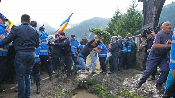Romanian crowd push their way into a graveyard