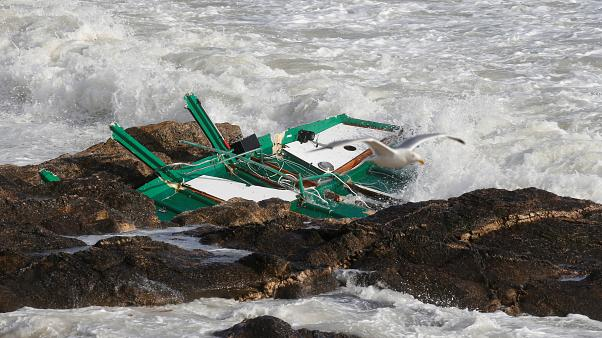 A piece of a capsized sea-rescue boat is seen on rocks during Storm Miguel