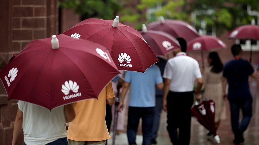 ضيوف يحملون مظلات عليها شعار هواوي بمقاطعة غواندونغ بالصين. أيار 2019