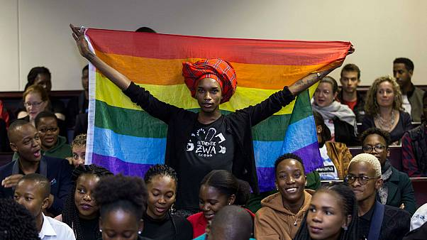 An activist holds up a rainbow flag to celebrate inside Botswana High Court