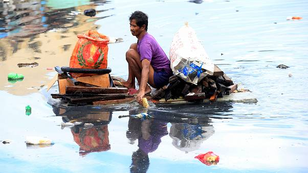Man uses an improvised banca to collect plastic materials in a polluted river in Manila