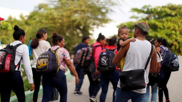 Migrantes caminan después de cruzar el río Suchiate en una balsa desde Tecun Uman, en Guatemala