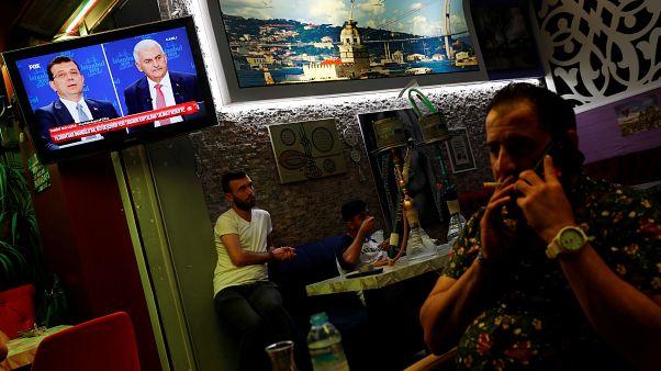 رواد مقهى في إسطنبول يتابعون البث الحي للمناظرة